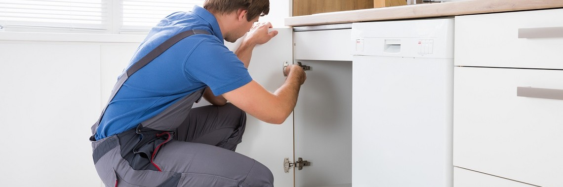 A Man Installing Soft Close Hinges In A Kitchen In Perth